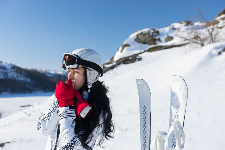 Female Skier Warming Hands on Sunny Mountainside