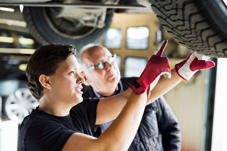 Young mechanic explaining tire problems to customer below car at auto repair shop