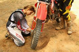 A woman working on a dirtbike tire