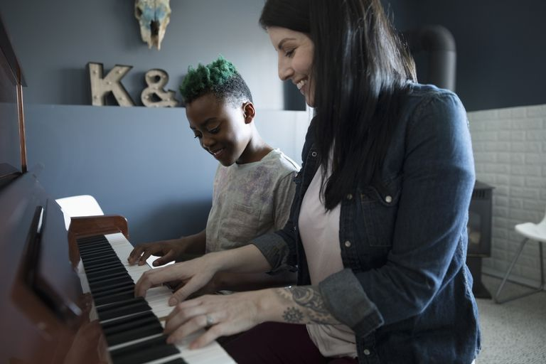 Mother teaching son piano lesson