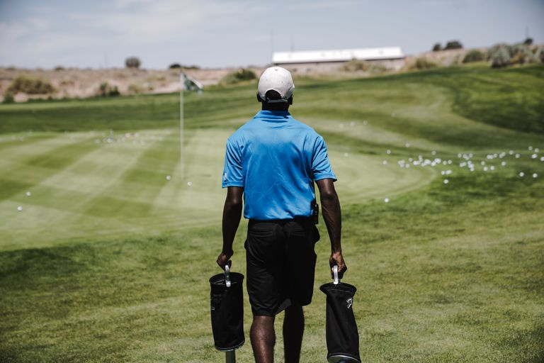 Man walking on the golf course carrying bags.