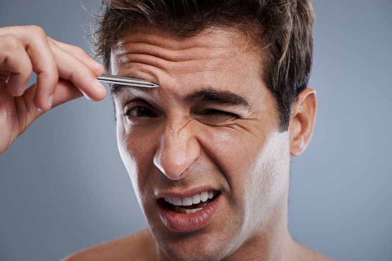 A man tweezing his eyebrows.