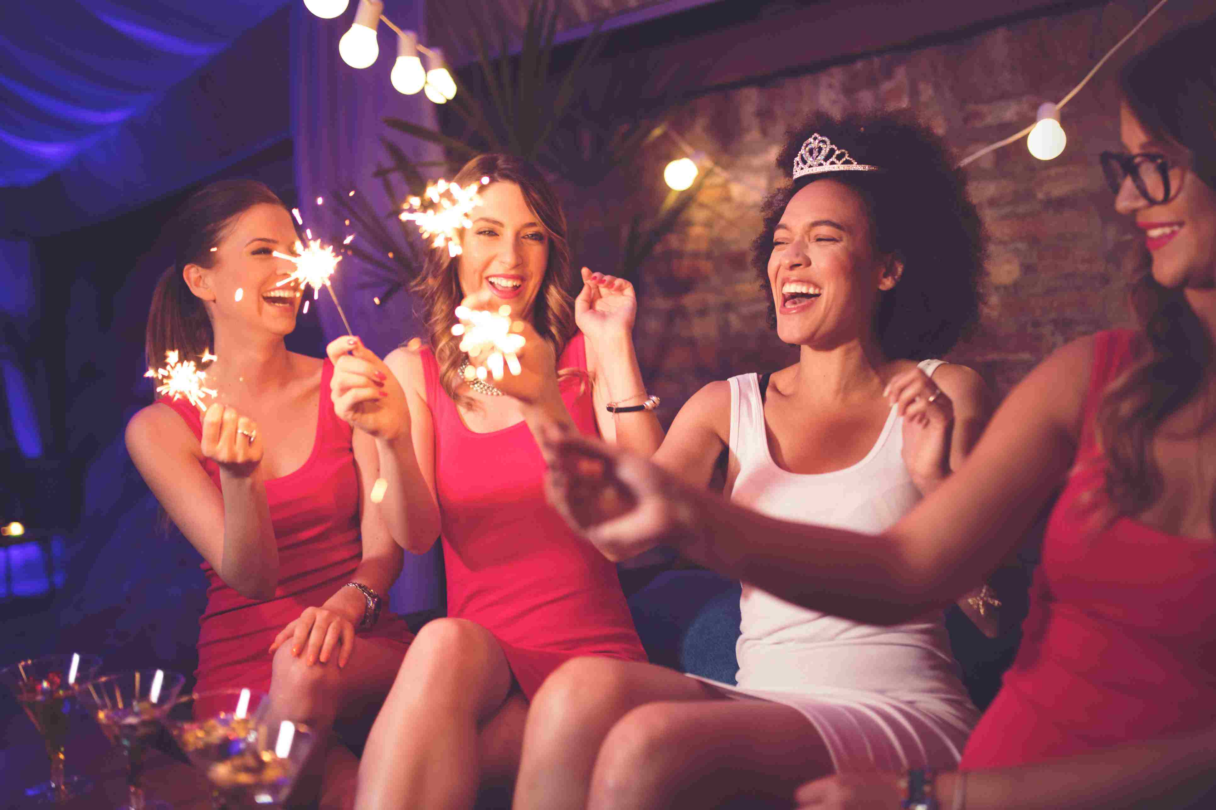 Women at a bachelorette party hold sparklers