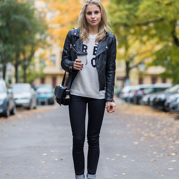 Street style photo of woman wearing black jeans and Adidas sneakers