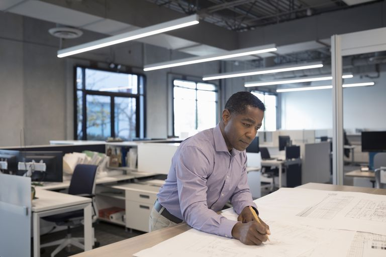 Male African American architect drafting and reviewing blueprints in office