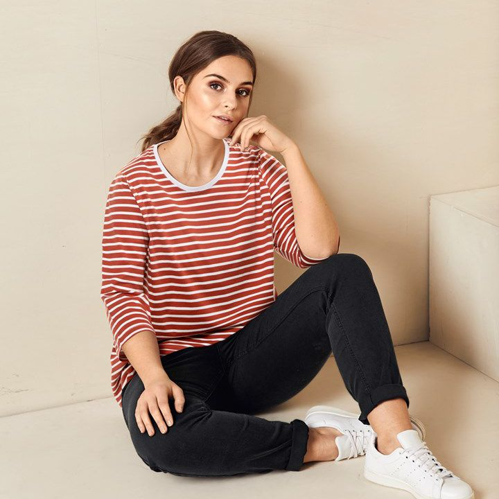 A woman sitting on the floor wearing a striped shirt and black jeans