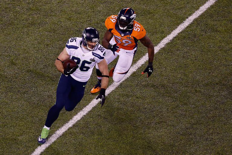 EAST RUTHERFORD, NJ - FEBRUARY 02: Tight end Zach Miller #86 of the Seattle Seahawks tries to avoid the tackle of outside linebacker Danny Trevathan #59 of the Denver Broncos during Super Bowl XLVIII at MetLife Stadium on February 2, 2014 in East Rutherford, New Jersey.