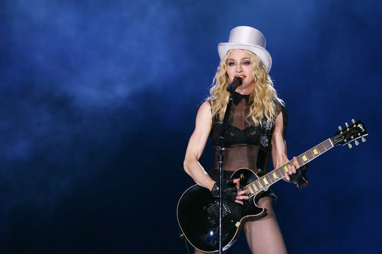Madonna performing in concert in a white top hat