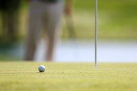 A golf ball on green next to the flagstick