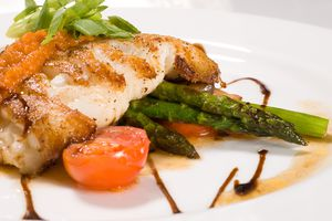 Lightly grilled catfish on a bed of vegetables.