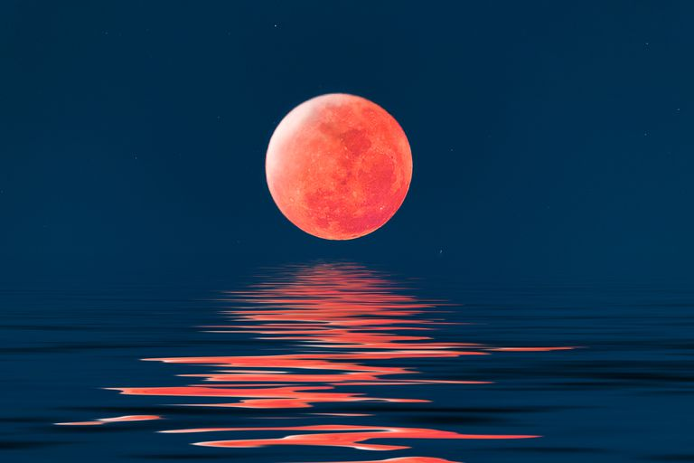 Super blue blood full moon over cold night water.