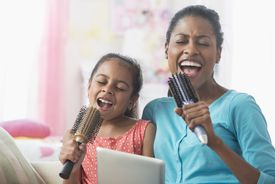 Hispanic mother and daughter singing with hairbrushes and digital tablet