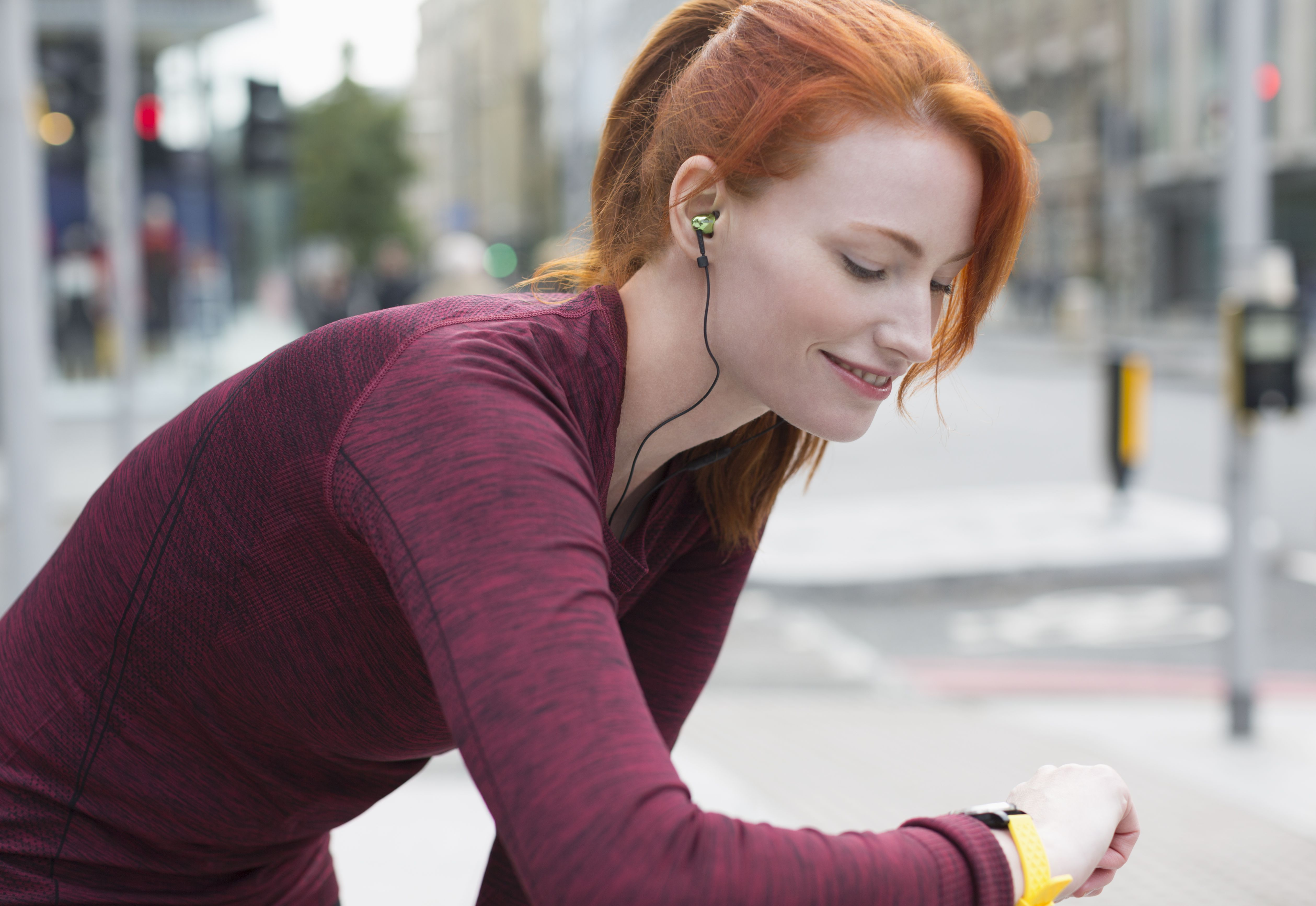 Smiling female runner with headphones checking smart watch