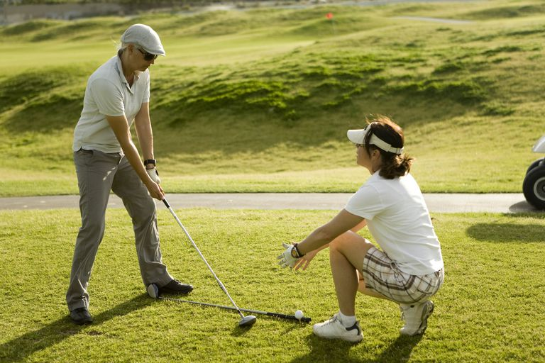 Beginner golfer taking lesson from instructor