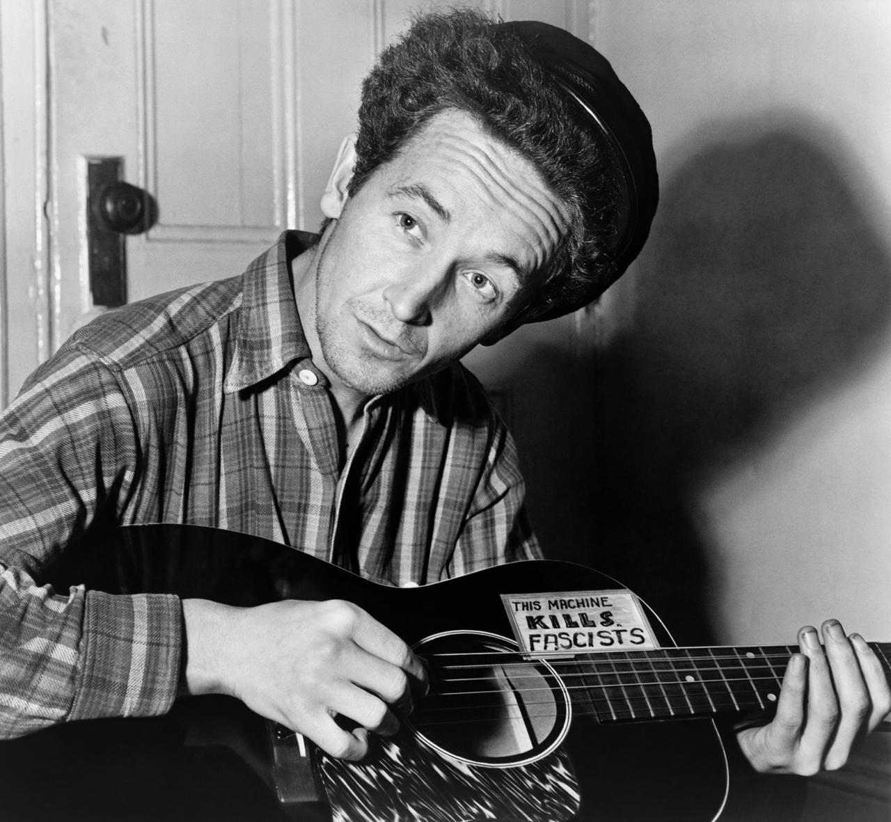 Woody Guthrie, half-length portrait, seated, facing front, playing a guitar that has a sticker attached reading: This Machine Kills Fascists