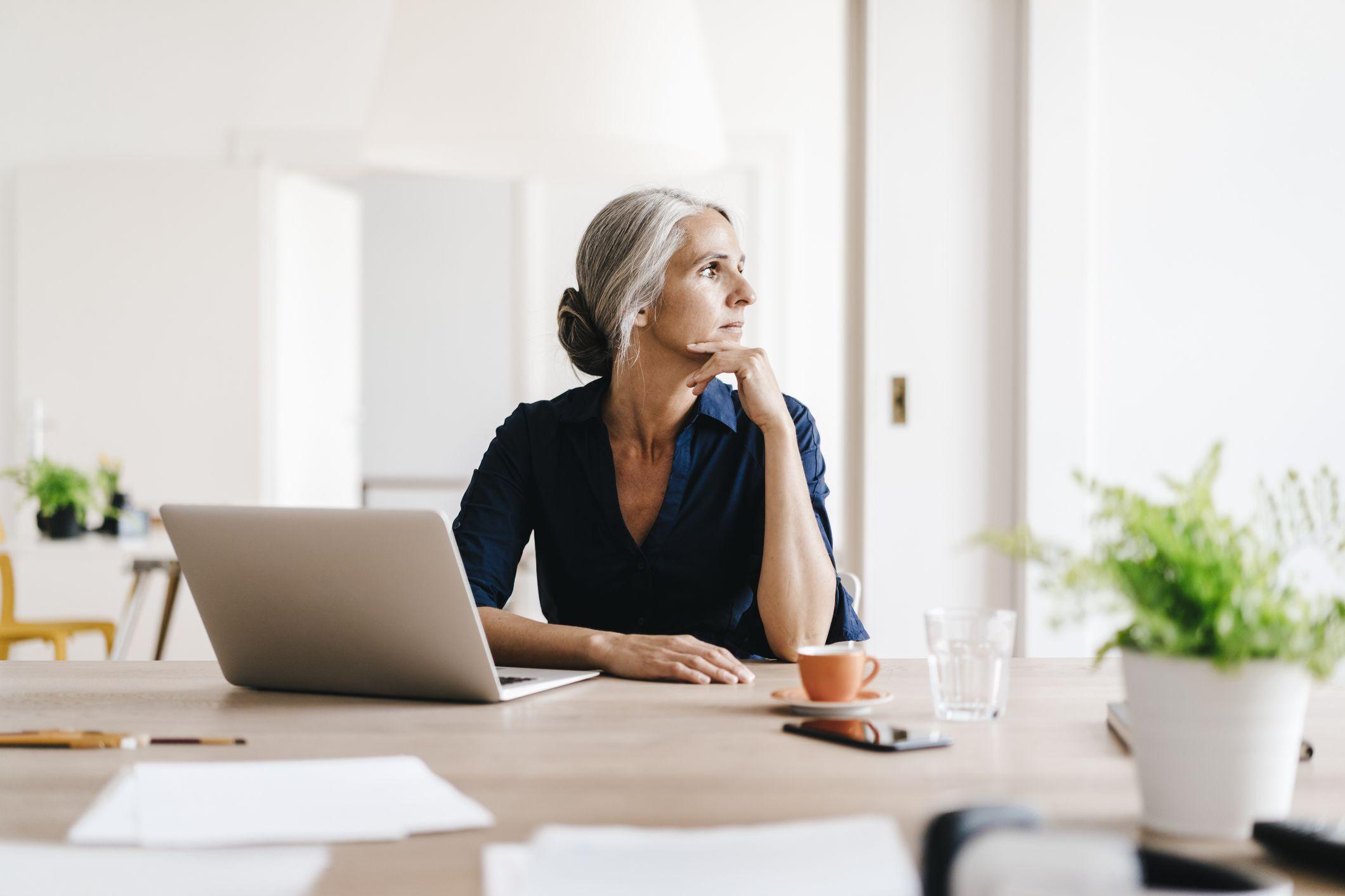 Woman sitting at laptop, thinking