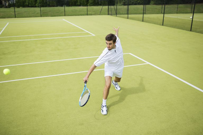 Tennis player swinging racket at ball on court