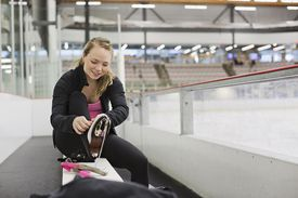 Female figure skater tying up skates in skating rink