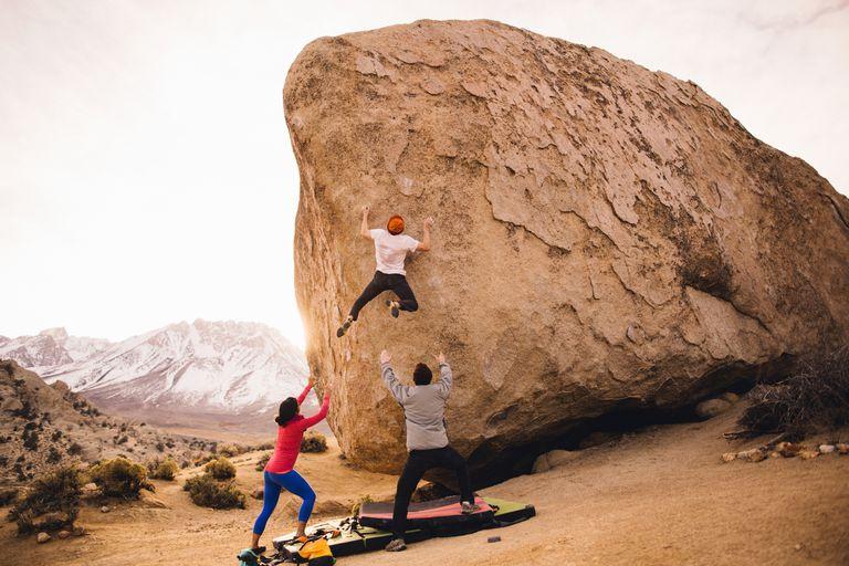 Friends climbing boulder, Buttermilk Boulders, Bishop, California, USA