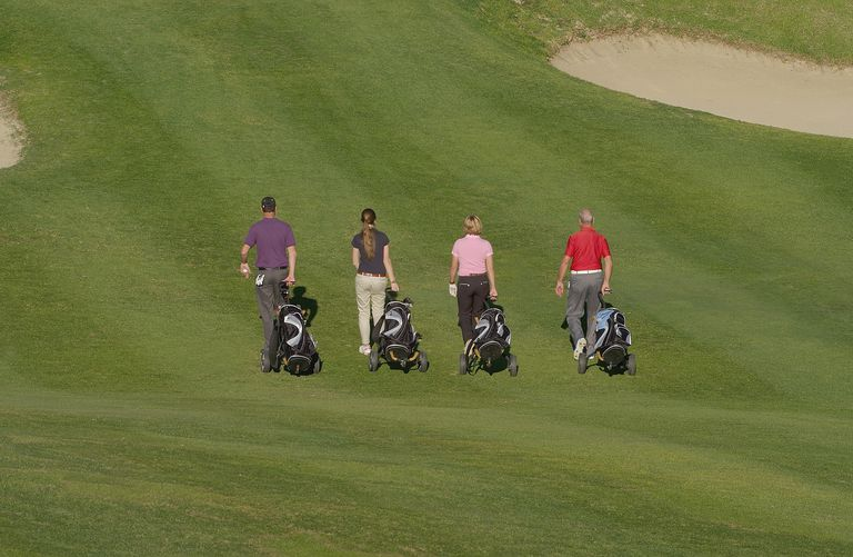4 golfers using pull carts