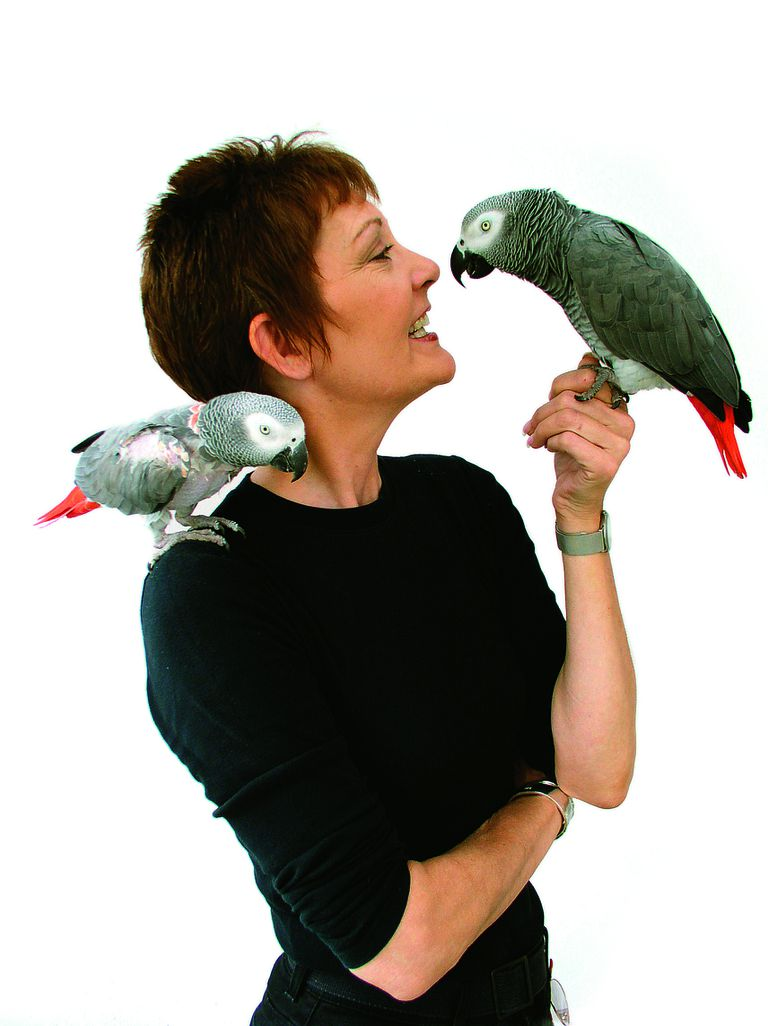Patricia Sund with two of her African Grey parrots