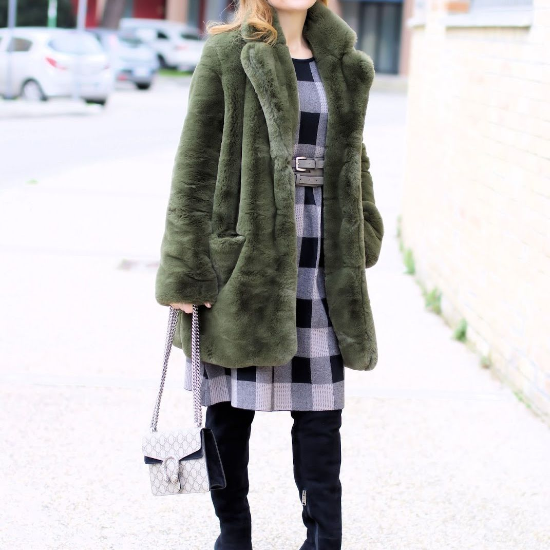 Woman wearing plaid dress and faux fur coat and black boots for winter style