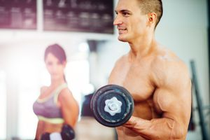 Image of muscular couple in topless lifting weights