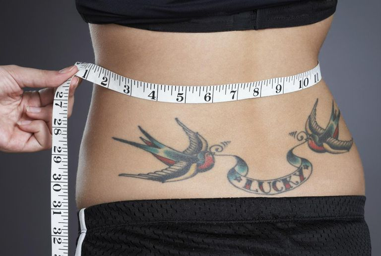 Young woman measuring waist with tape, with 'lucky' tattoo