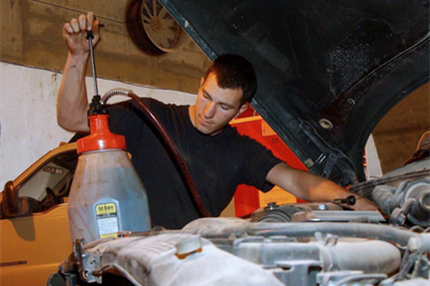 mechanic using a transmission fluid pump to add fluid to vehicle