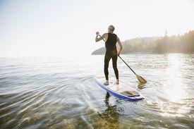 Senior man paddle boarding on ocean
