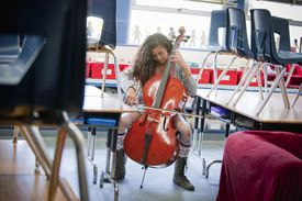 Girl [11] practicing cello after school