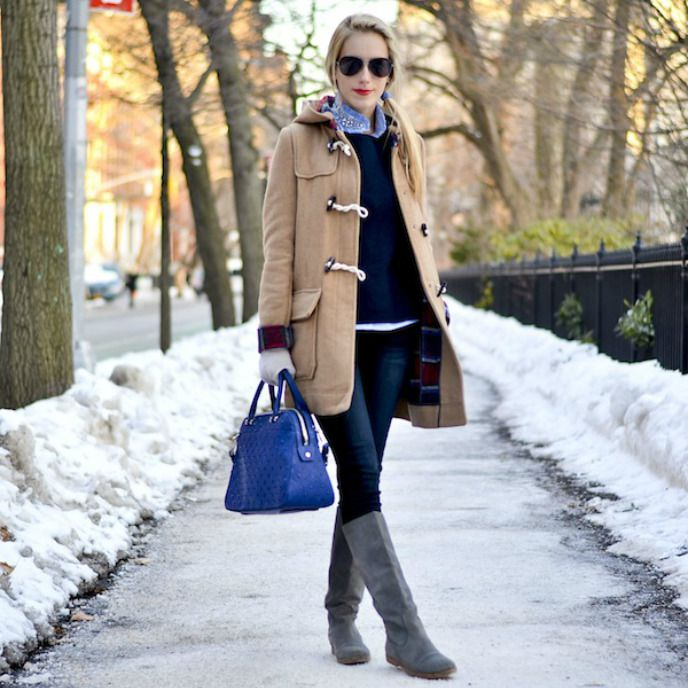 Woman in duffel coat and jeans and tall boots in winter scene