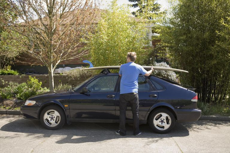 Man loading surfboard onto car roof