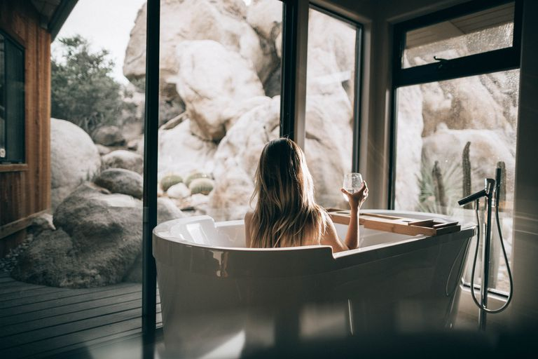 Woman in bathtub holding glass of wine