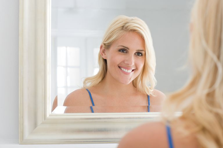 blonde woman smiling in mirror