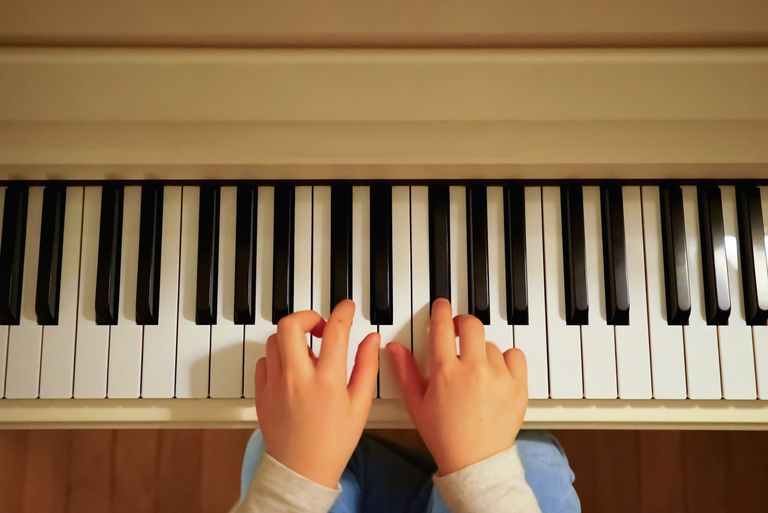 Child's hands on a piano keyboard.