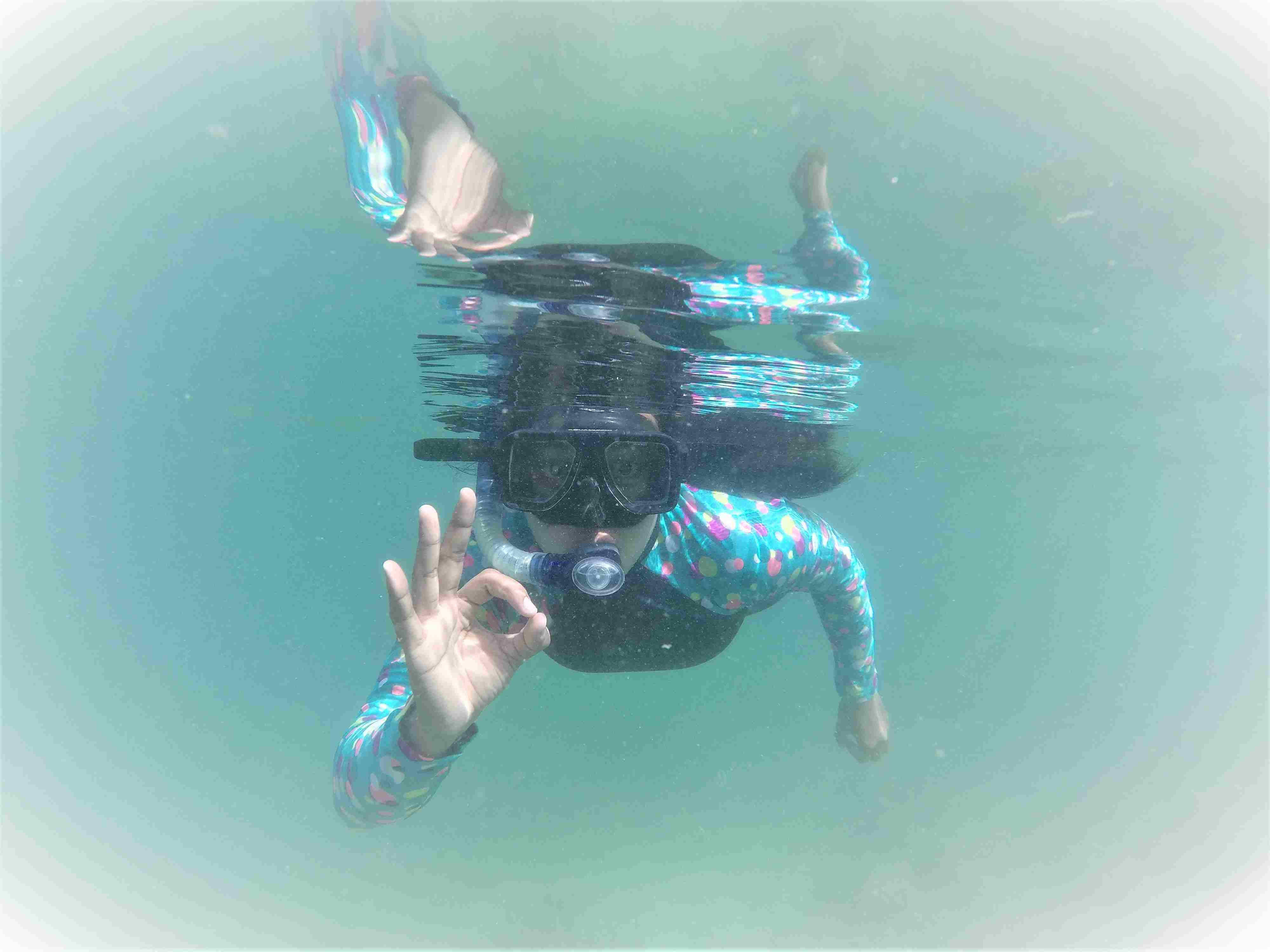 Portrait Of Scuba Diver Gesturing Ok Sign While Swimming In Sea