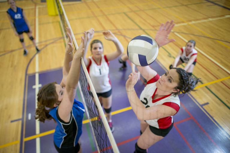 Volleyball player about to spike volleyball over net