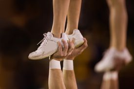 closeup of the shoes of a cheerleader being lifted
