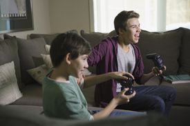 Excited brothers playing video games on sofa