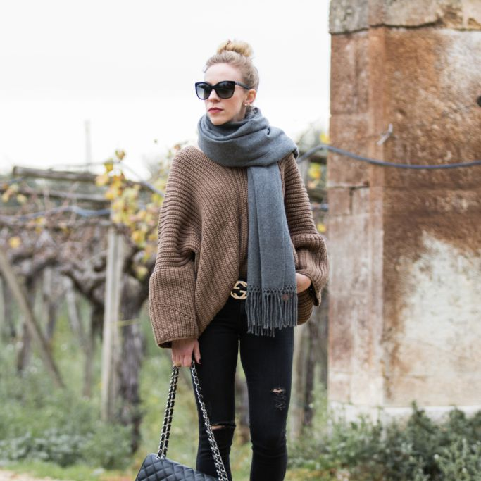 Woman in black jeans and sweater and big scarf for fall or winter fashion