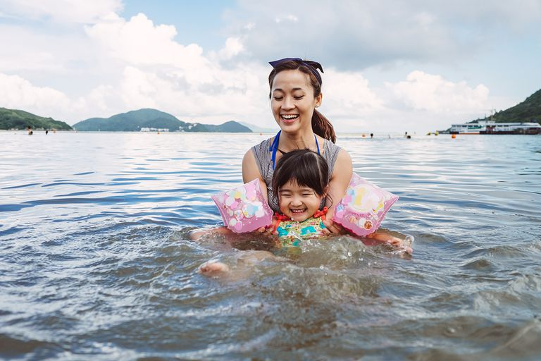 Mom teaching toddler to swim in a body of water