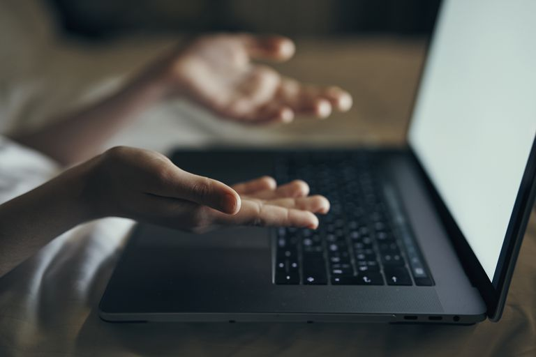 Hands of Caucasian woman gesturing at laptop in bed