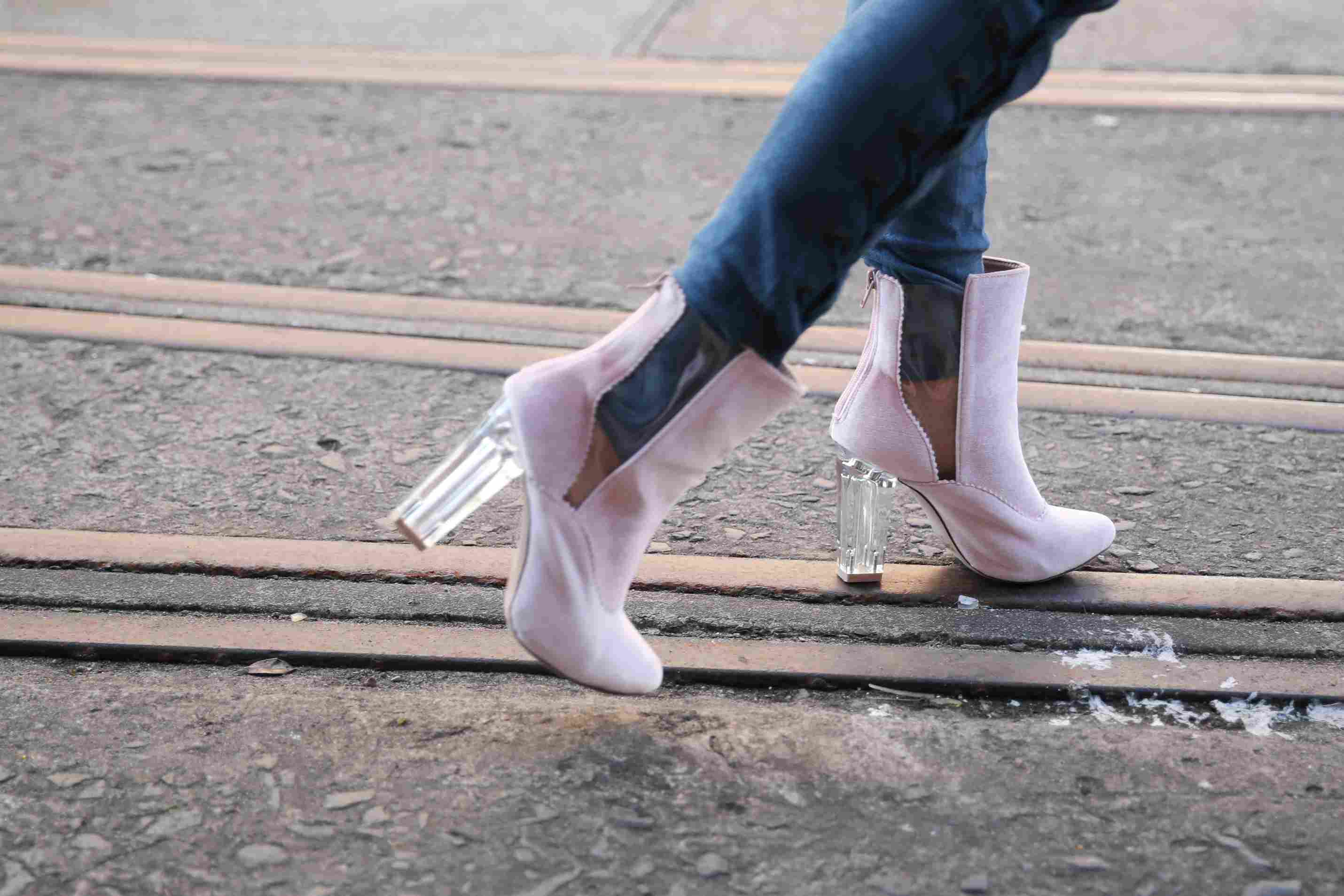 Woman's legs in skinny jeans and white ankle boots