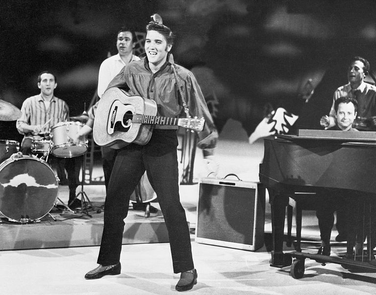 Elvis rehearsing on stage, black and white photo.