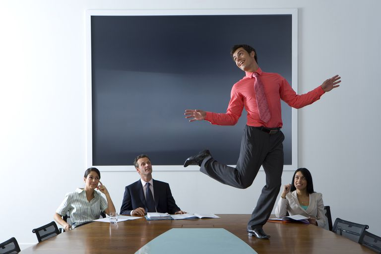 Man dancing on office conference table during meeting