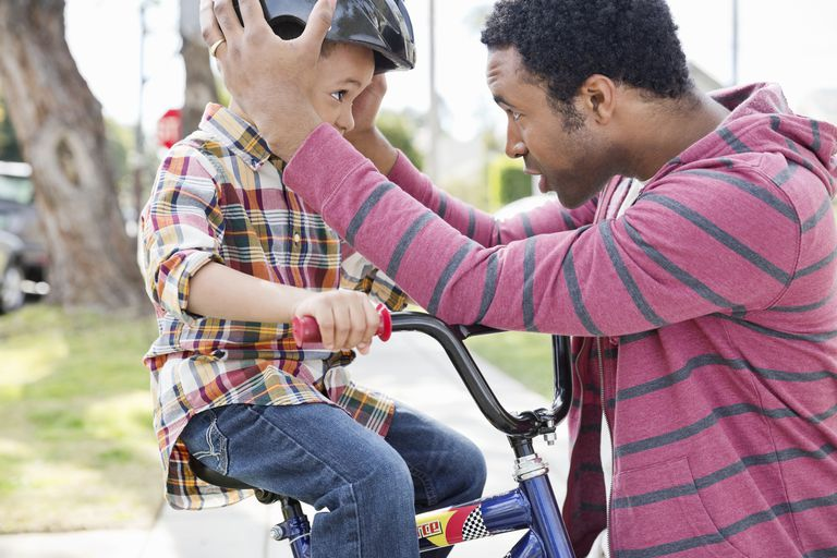 father adjusting son's bike helmet