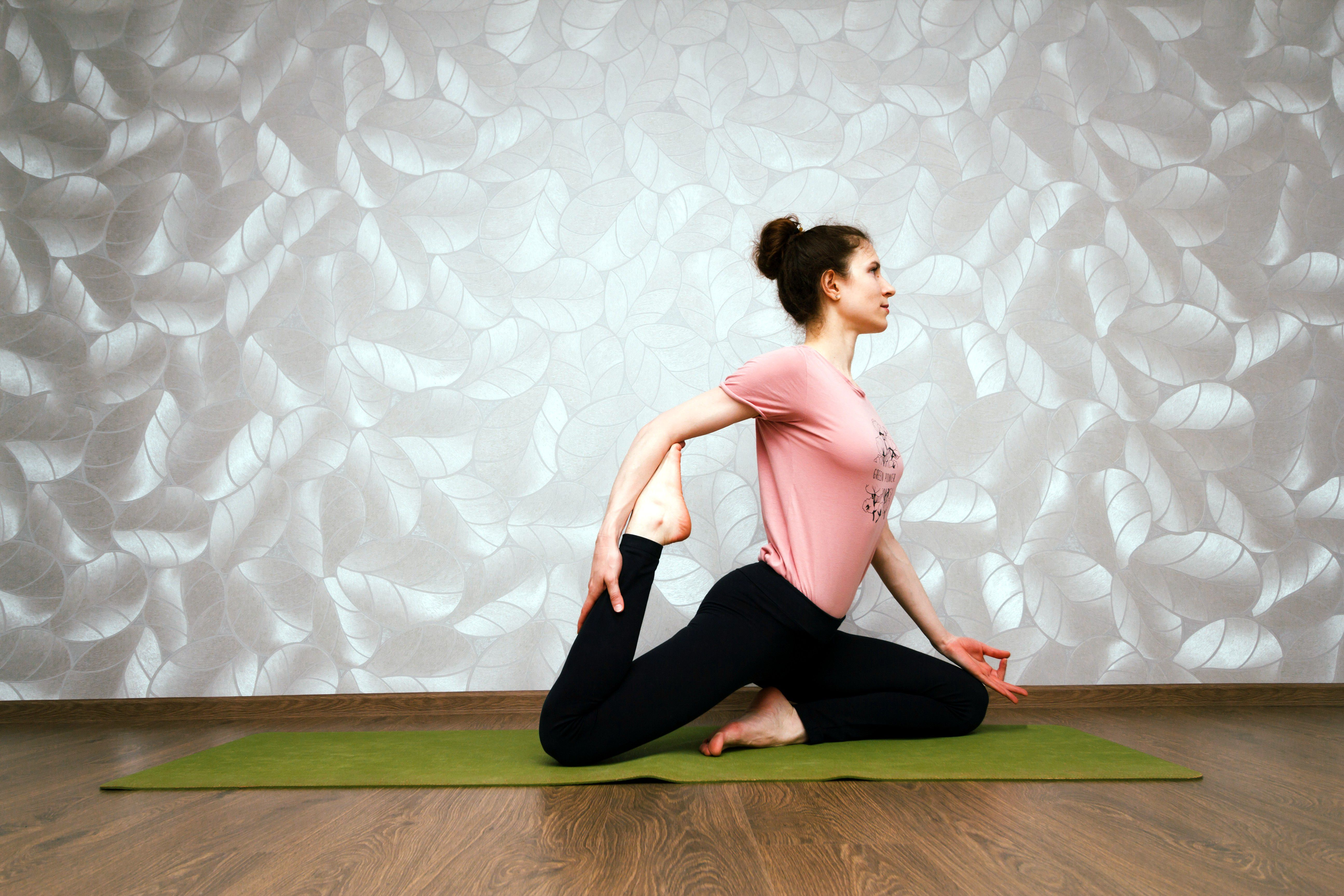 A woman stretches out her quadriceps muscle on a yoga mat