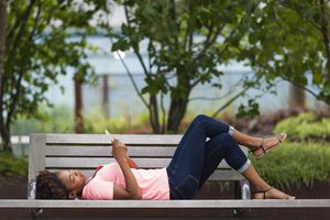 Woman lying on a park bench in jeans