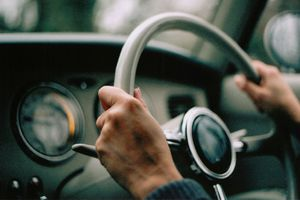 Hands on the steering wheel of a classic car
